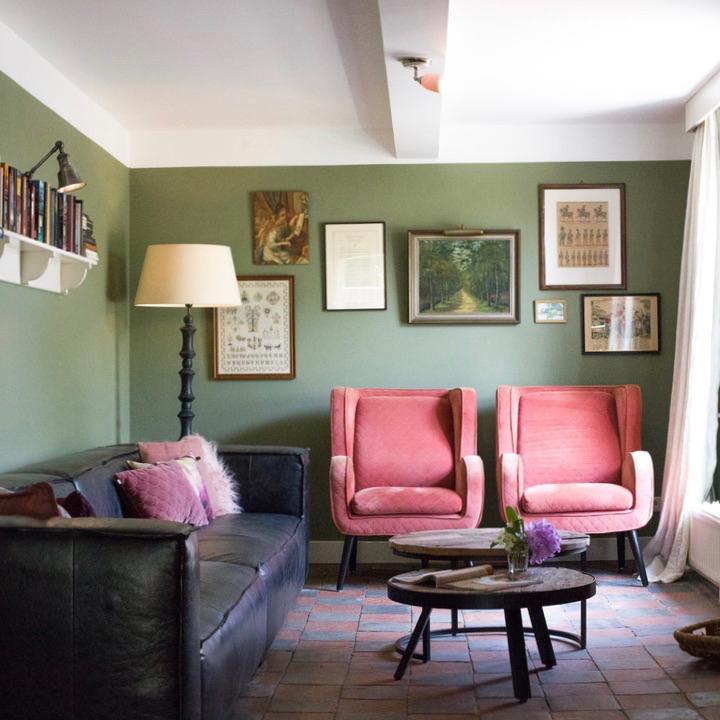 Woonkamer met roze fauteuils, een hangbank en groene muren