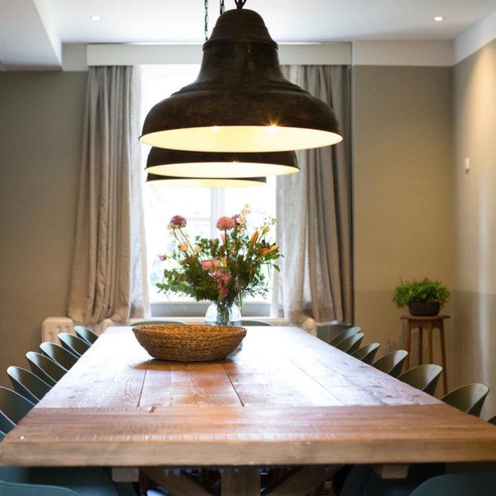 Lange eettafel met 12 stoelen eromheen