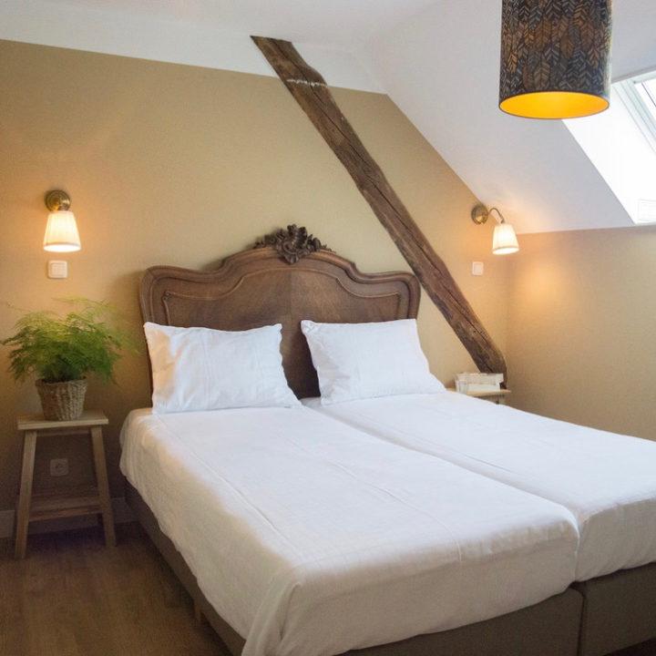 Slaapkamer met opgemaakt bed met antiek hoofdeinde