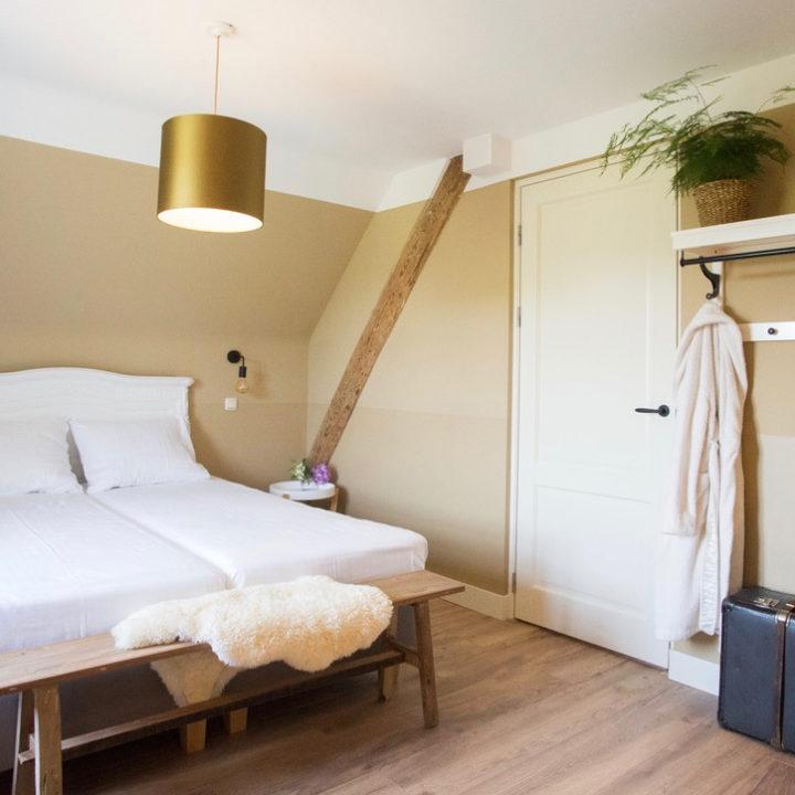 Slaapkamer met tweepersoons bed, crèmekleurige muren, een houten bankje met bontje erop