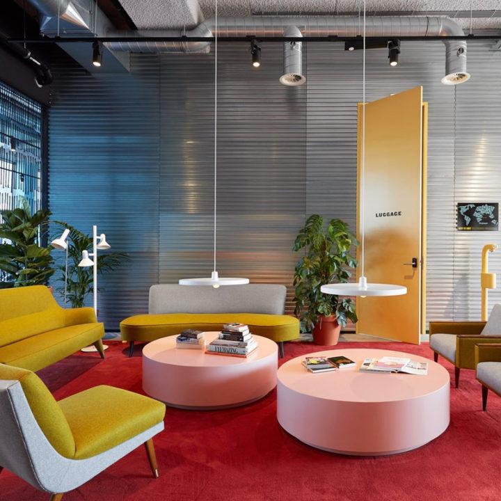 Bijzondere loungehoek met gele banken, roze tafels