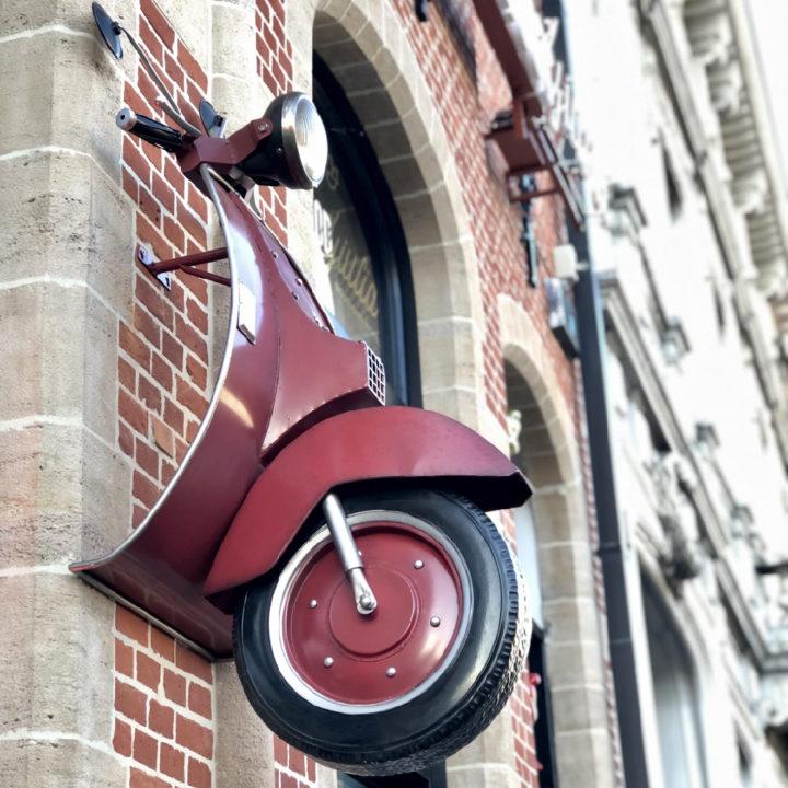 Rode vintage scooter aan de buitenwand van het hotel