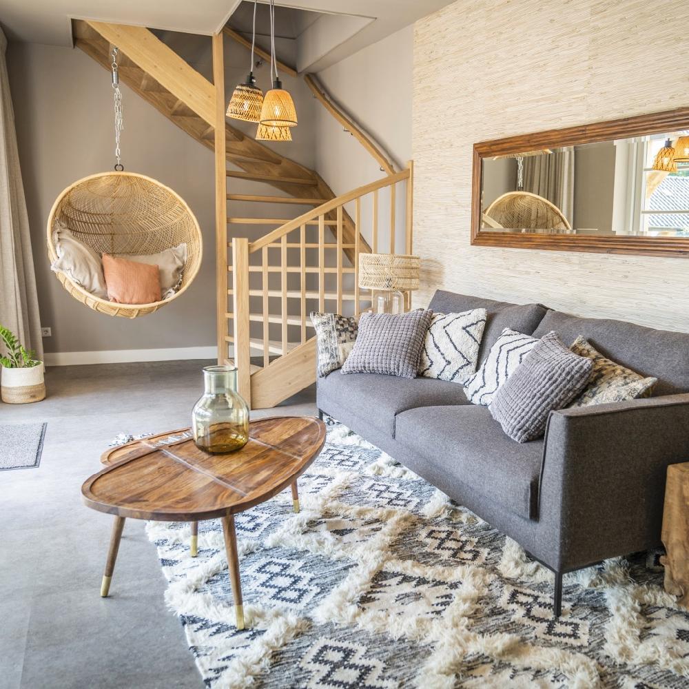 Zithoek met grijze bank en hangstoel in een van de suites
