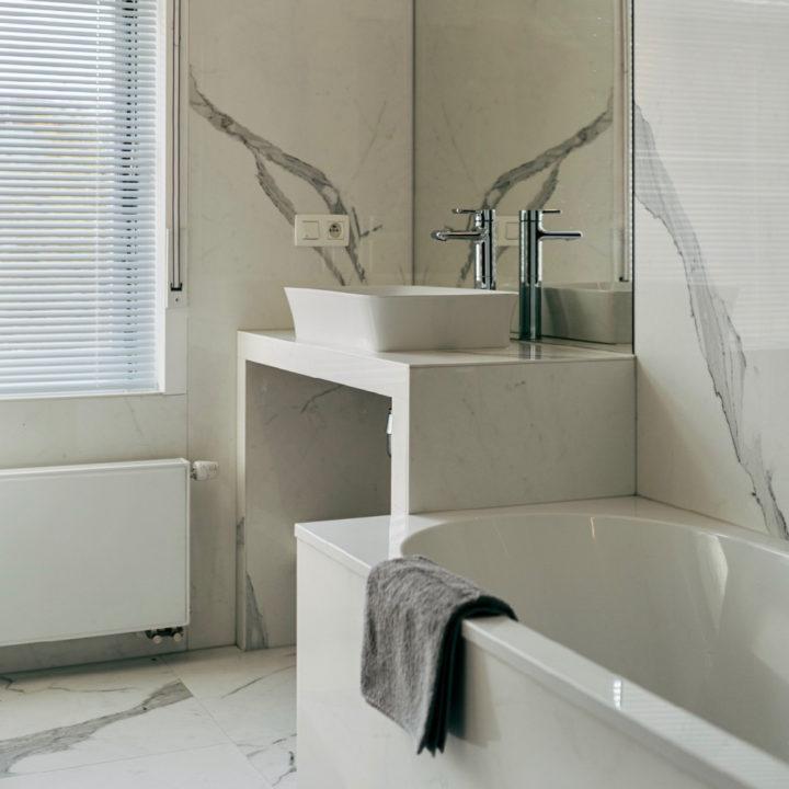 Badkamer met bad, marmer en veel wit