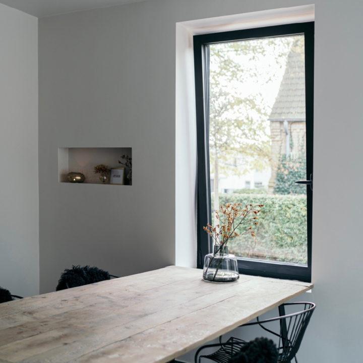 Eettafel met ruw houten blad voor het raam