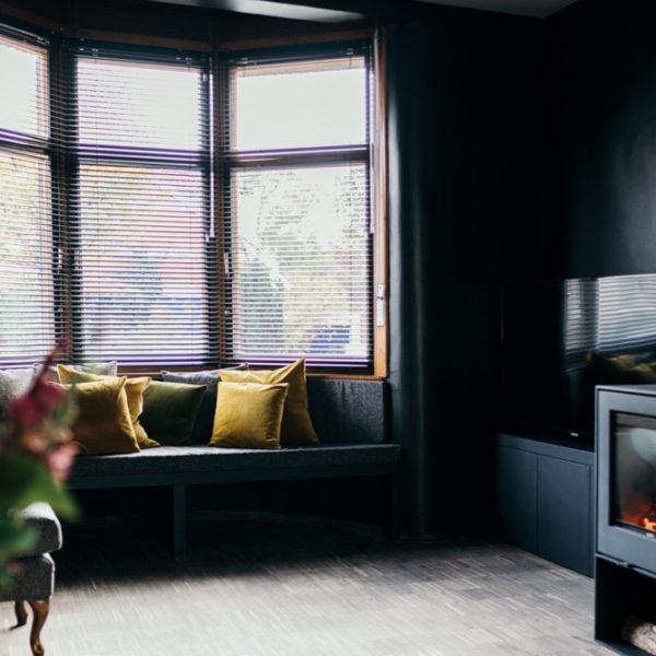 Zwarte woonkamer met zithoek in de erker en houtkachel