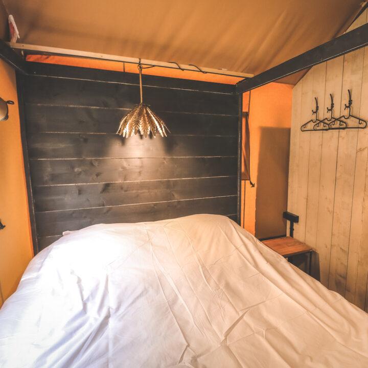 Opgemaakt tweepersoons bed in een safaritent in Toscane