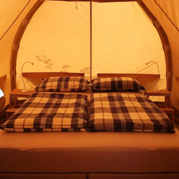 Opgemaakt bed in een huurtent