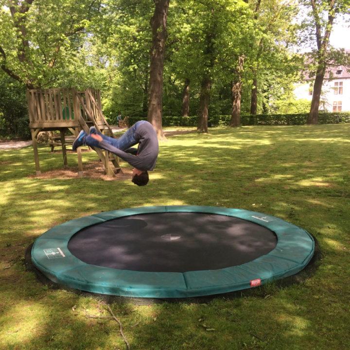 Jongen doet salto op een trampoline