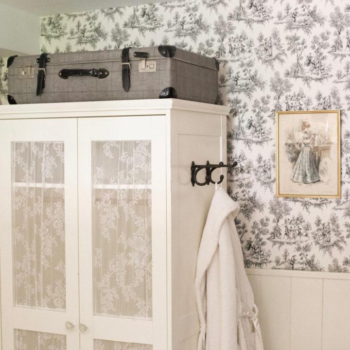 Slaapkamer met romantisch behang, een witte kast en koffer op de kast