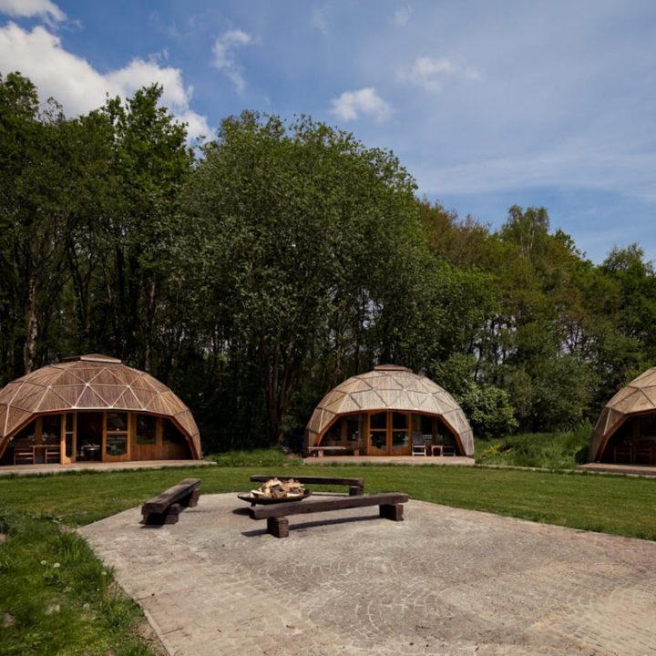 Veld met drie dome tenten op camping Buitenland