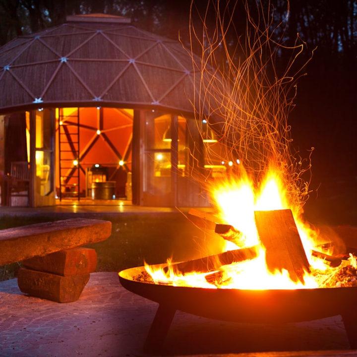 Gloeiend vuur temidden van dometenten op camping Buitenland
