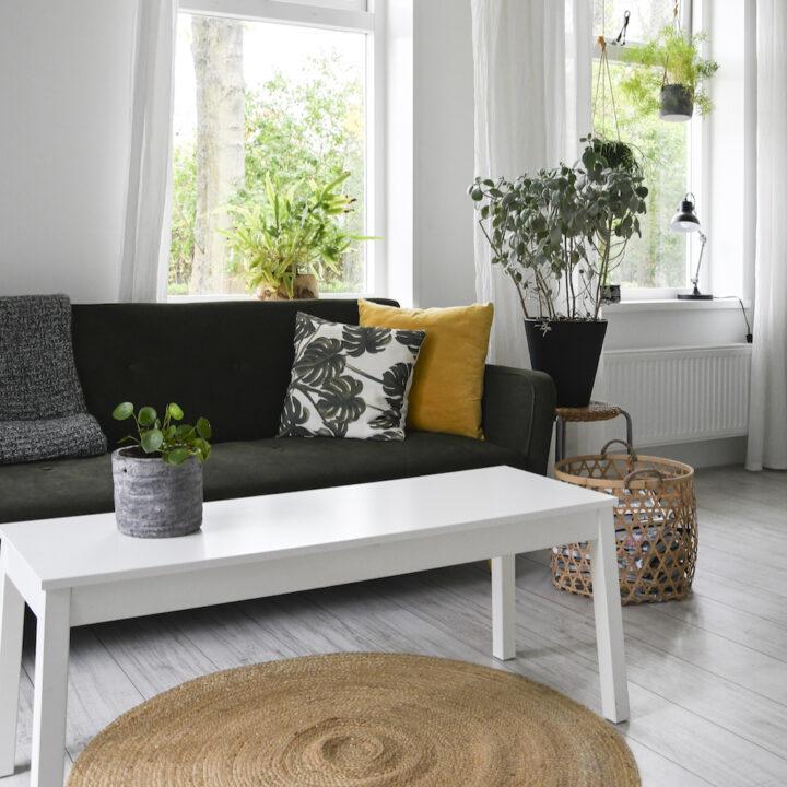 Lichte woonkamer met bank, rieten mand en rieten lamp