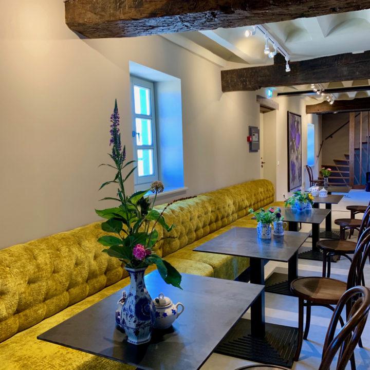 Lange gele muurbank met tafeltjes ervoor
