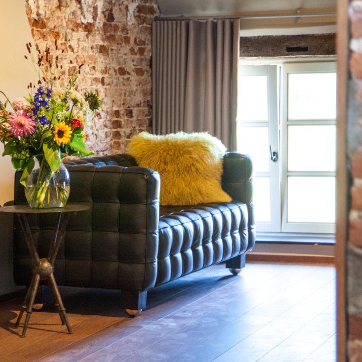 Leren groen bank met vaas met bloemen in het boutique hotel