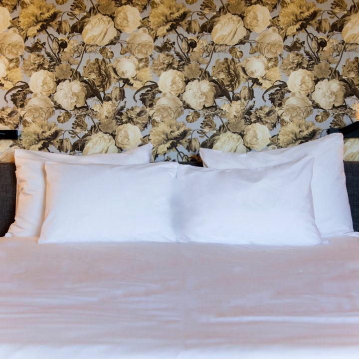 Tweepersoonsbed met bloemenbehang in het boutique hotel