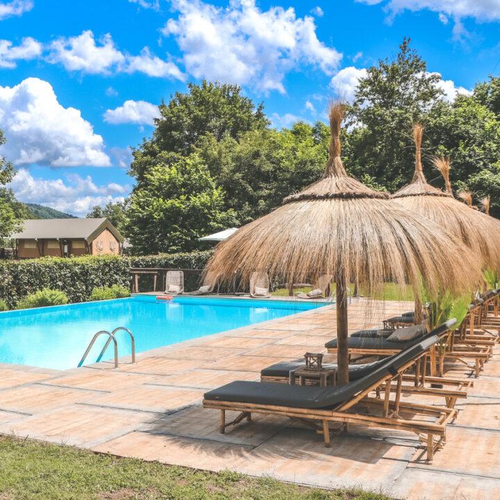 Zwembad met ligbedden en rieten parasols