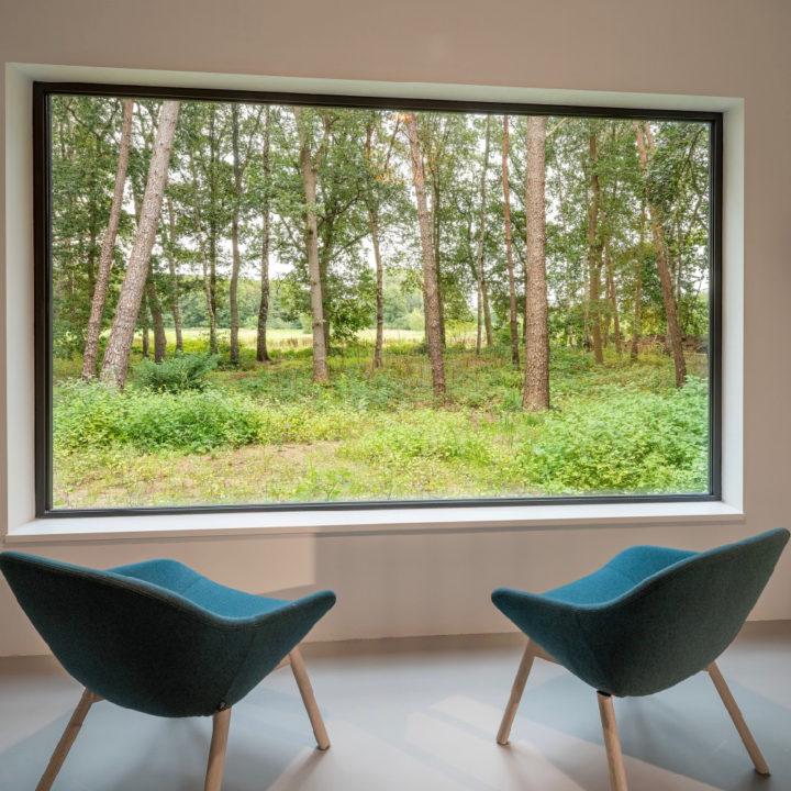 Twee fauteuils voor een groot raam met zicht op de natuur