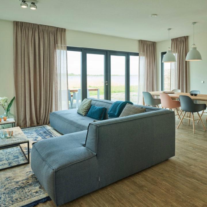 Ruime woonkamer met zithoek en grote ramen