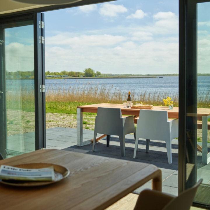 Openslaande deuren naar het terras met zicht over het Lauwersmeer