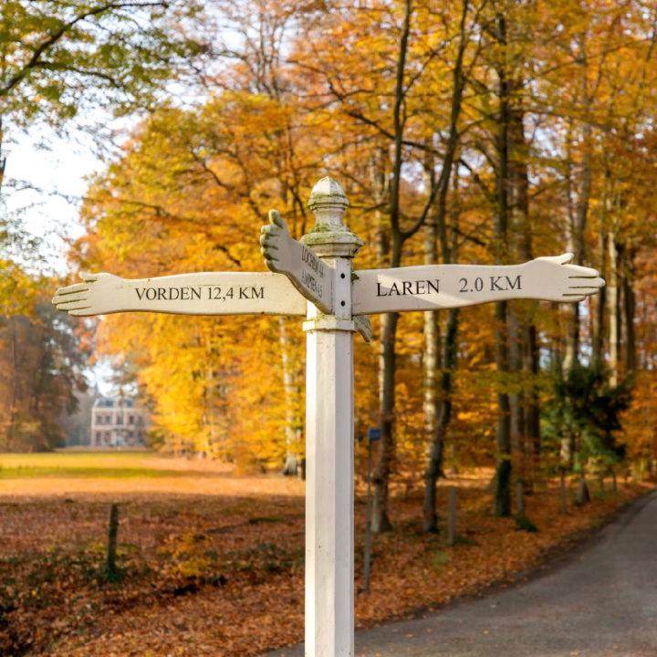 Wit authentiek straatbordje met de richting voor Laren, Vorden