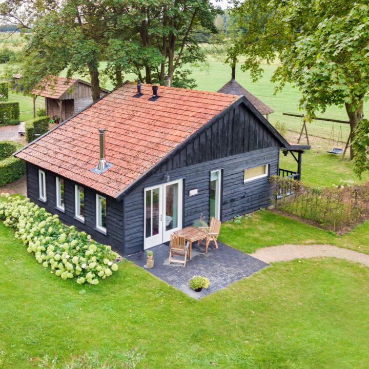 Luchtfoto van het zwarte houten huisje in de Achterhoek