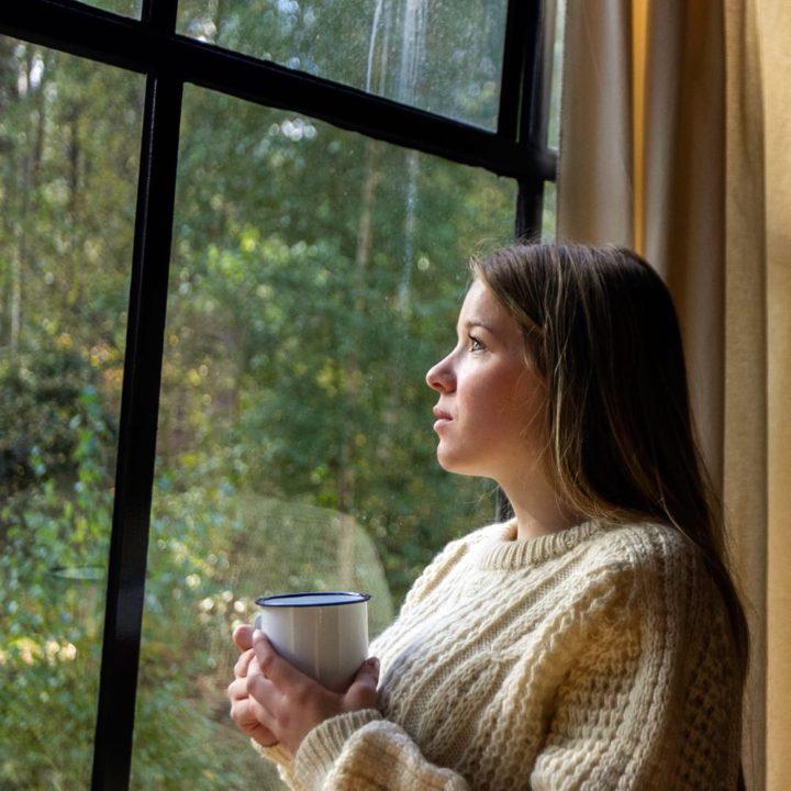 Jonge vrouw kijkt door het raam naar buiten met een kop koffie in haar handen