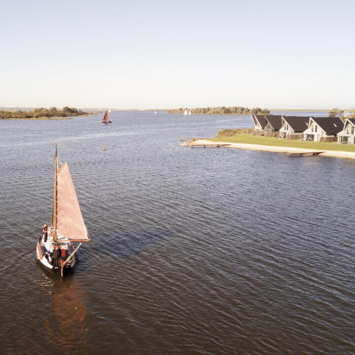 Zeilboot op het Lauwersmeer met vakantiehuizen op de oever