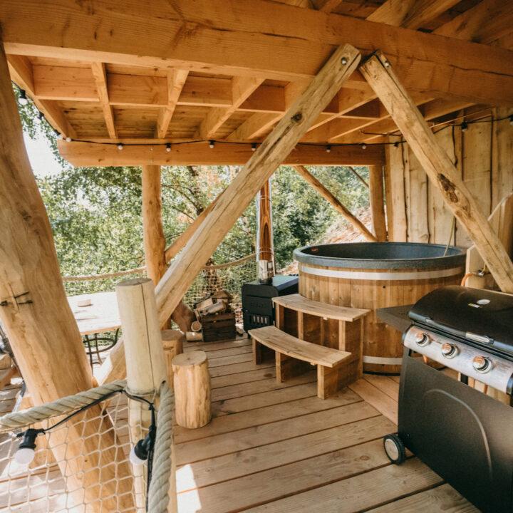 Boomhut met een hot tub op een overdekt terras