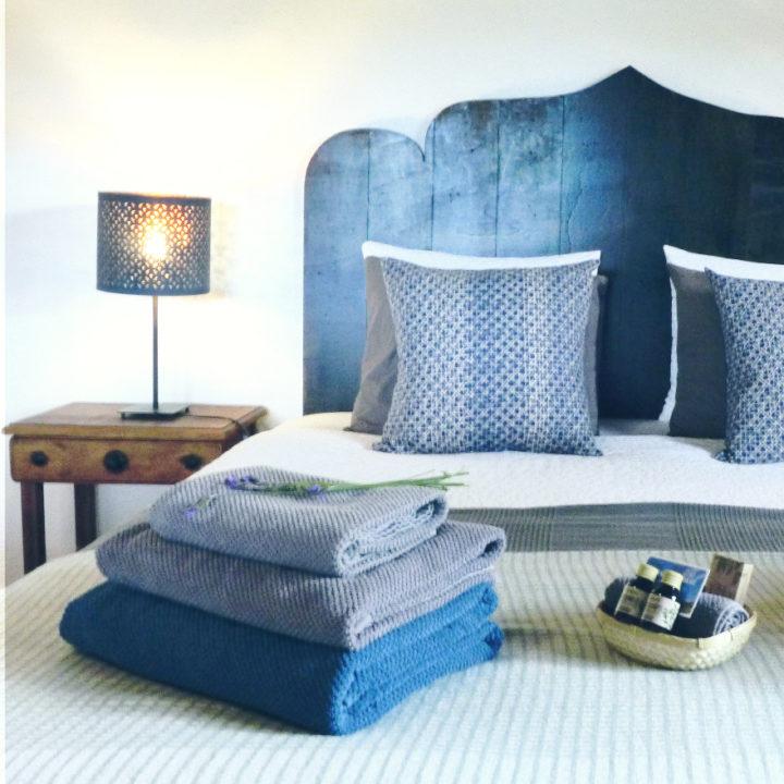 Stapel handdoeken en badproducten op bed in de B&B