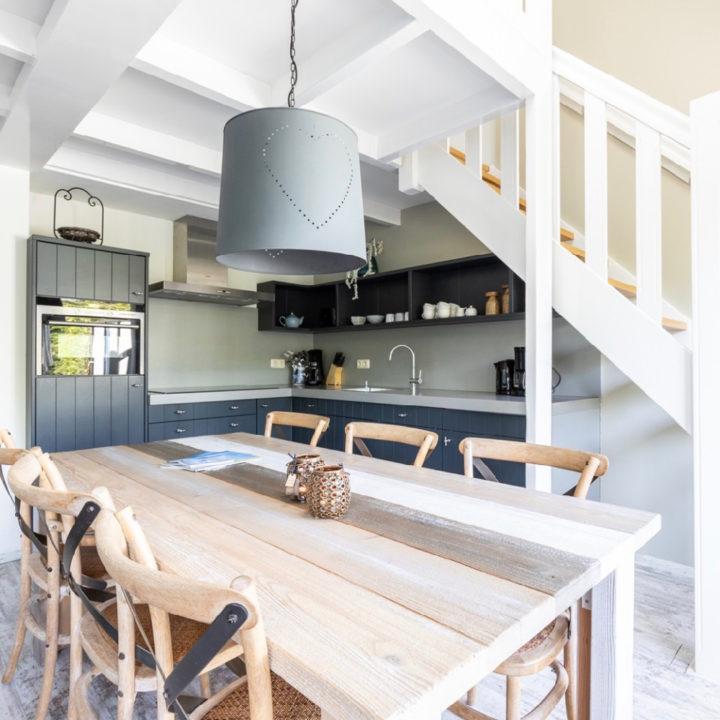 Eettafel van steigerplanken met grijze open keuken