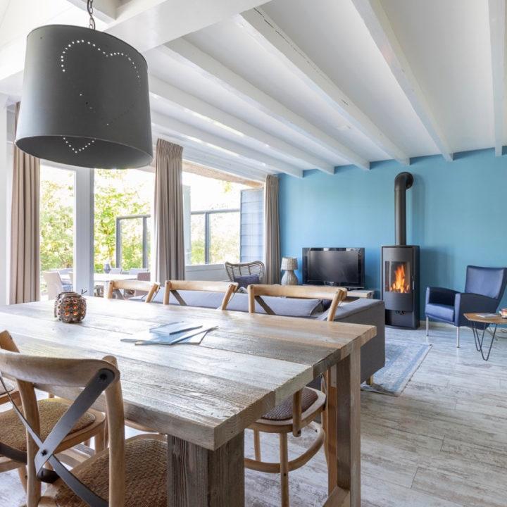 Eethoek met zicht op de woonkamer met blauwe wand en brandende kachel