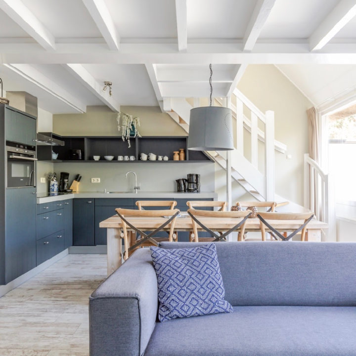 Grijze zitbank met zicht op de keuken