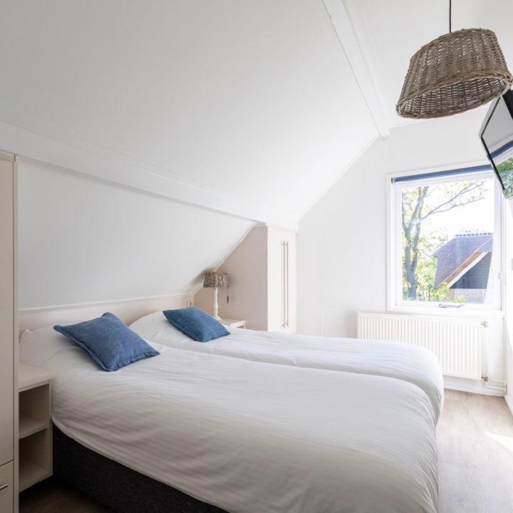 Ruime slaapkamer met opgemaakt bed