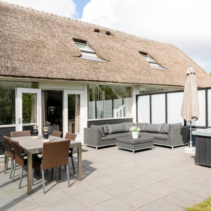 Loungehoek en eettafel op een groot terras in de zon voor de vakantievilla