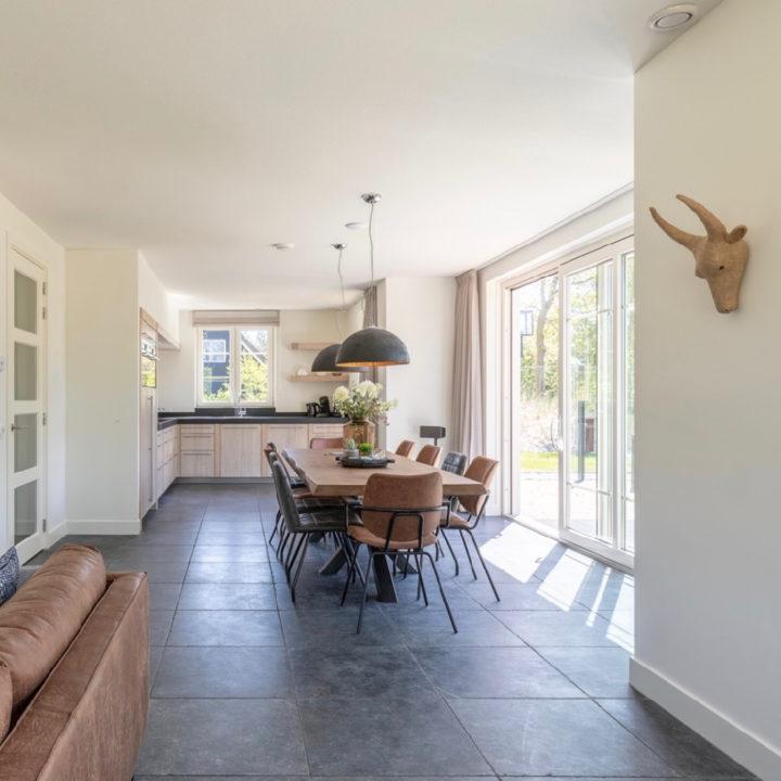 Modern ruimte in een vakantiehuis met lange eettafel, schuifdeuren naar een groot terras