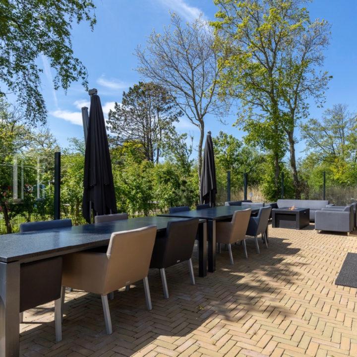 Lange eettafel met stoelen op het terras