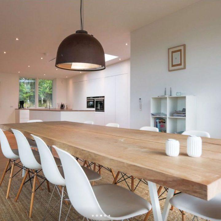 Eettafel van licht hout met witte kuipstoelen
