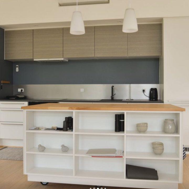 Keuken met wooneiland met open zijkant met planken voor servies