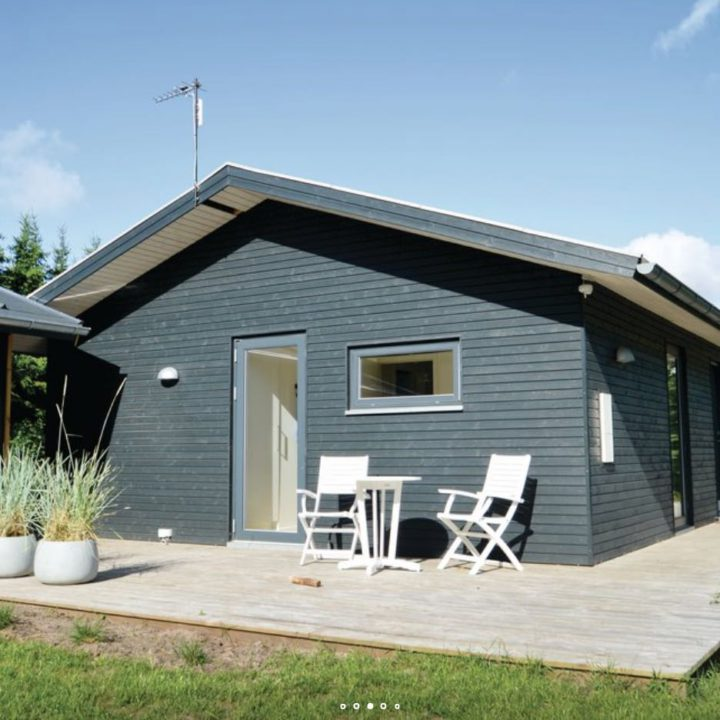 Zwart vakantiehuis met witte stoeltjes op het terras