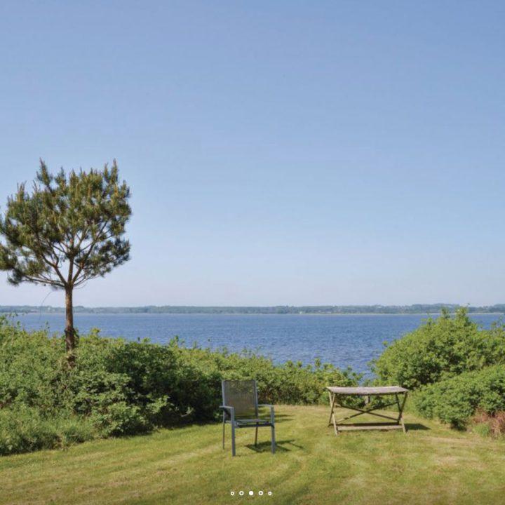 Tuin met grasveld, stoeltje, tafeltje en zicht op een meer
