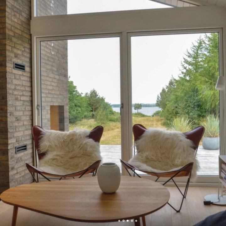 Vlinderstoelen met bontjes voor de ramen van een vakantiehuis
