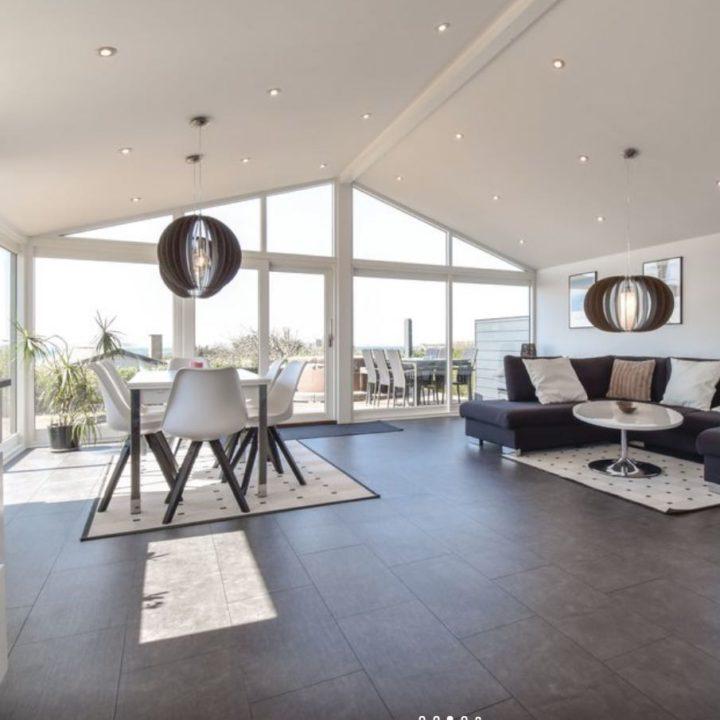 Open woonkamer met eethoek en grote glazen gevel