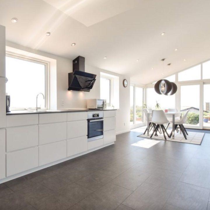 Strakke witte keuken en zithoek, met zicht op zee