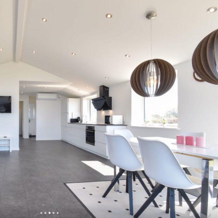 Lichte open ruimte met witte design keuken en witte design eethoek