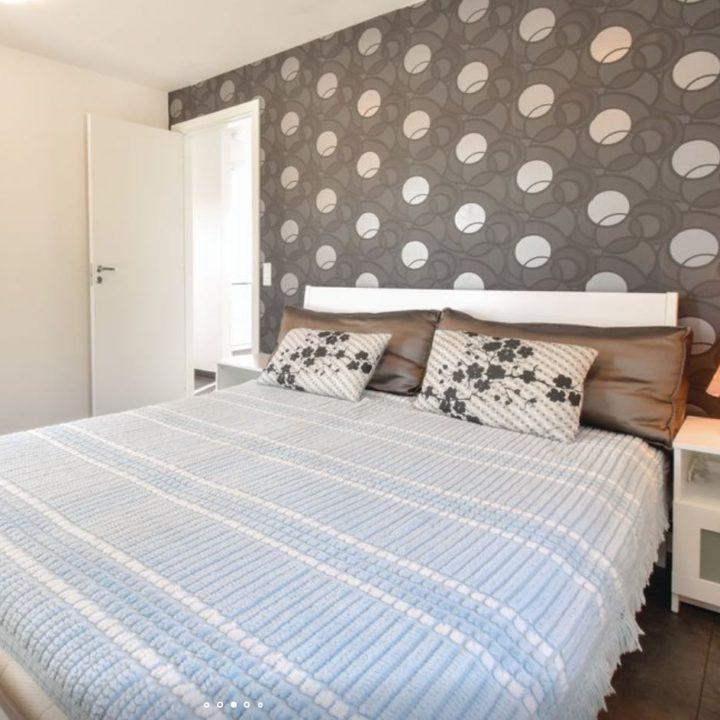 Slaapkamer met opgemaakt bed met blauwe sprei en bolletjesbehang