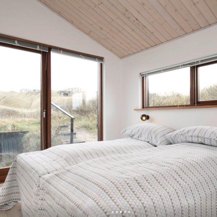 Opgemaakt bed voor grote ramen met zicht op de duinen