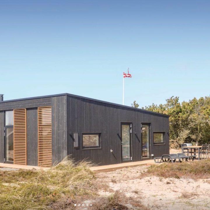 Zwart houten vakantiehuis met wapperende Deense vlag
