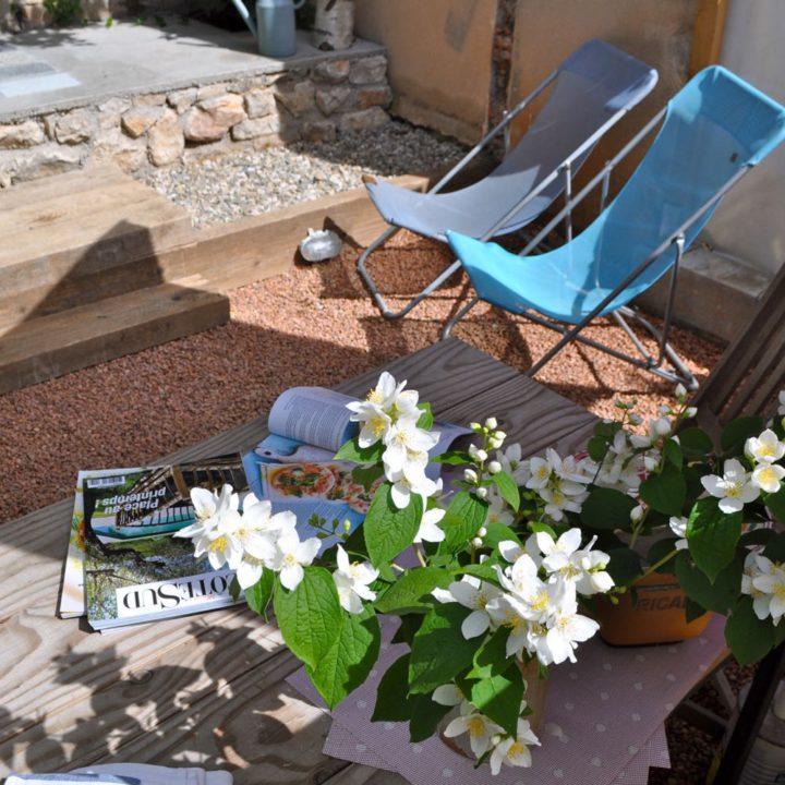 Ligstoelen in de tuin van het vakantiehuis met een stapel tijdschriften