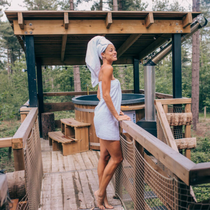 Dame met handdoek om bij de hot tub bij de cabin